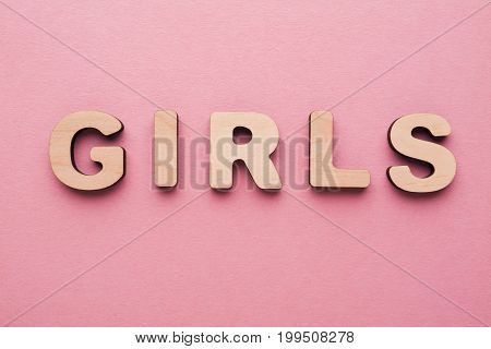 Word Girls made of wooden letters on blue background. Baby waiting concept