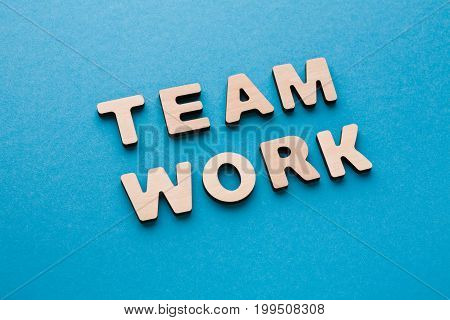 Word Teamwork on blue background. Cooperation, togetherness, partnership concept