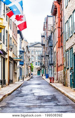 Quebec City Canada - May 30 2017: Empty narrow European street in upper old town called Rue Garneau with flags and wet road