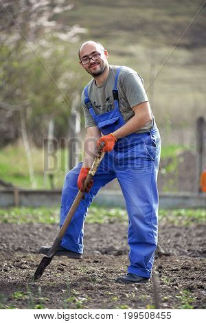 Portrait of a smiling man gardening in his garden on a lovely spring day color toned image . The gardener digs the garden with a shovel