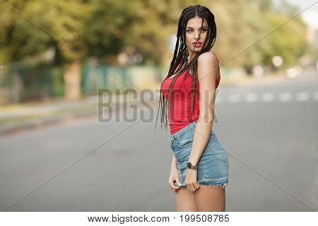Young beautiful and sexy girl with slim sun tanned attractive body dressed in jeans skirt is posing outdoor in the summer city. Woman with trendy pigtails
