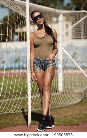 Beautiful young sexy woman in jeans shorts at summer on football stadium