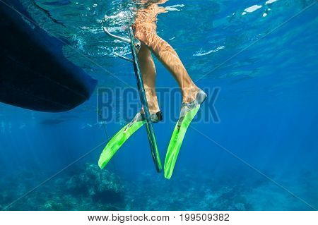 Child in snorkelling fins stand on divers boat ladder for diving underwater in tropical coral reef sea pool. Travel lifestyle water sport outdoor adventure on family summer beach holiday with kids.