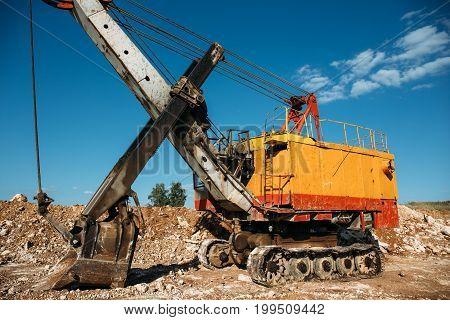 Quarry orange heavy duty excavator loader at blue sky background