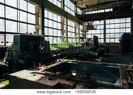 Abandoned factory room with large windows and iron equipment, abandoned industrial concept, toned