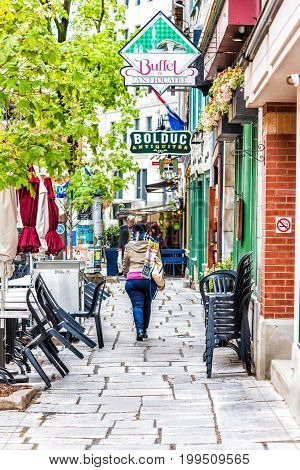 Quebec City Canada - May 30 2017: Lower old town street rue Saint Paul with cobblestone sidewalk and woman walking by shops stores and restaurants