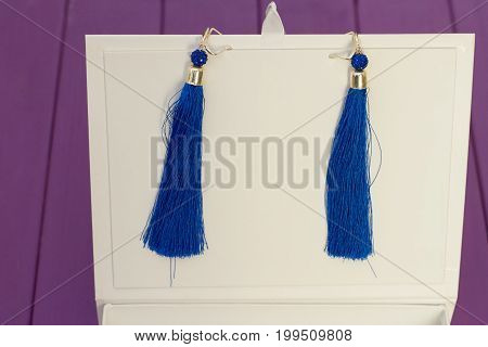 Handmade blue threaded earrings and a white box on a purple wooden background