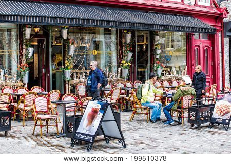 Quebec City Canada - May 30 2017: Lower old town street with cobblestone street and restaurant tables on outside patio