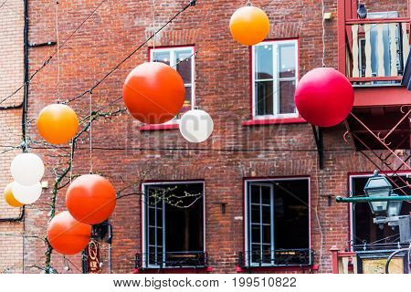 Quebec City Canada - May 30 2017: Lower old town cobblestone street called Sous le Fort with restaurants and hanging colorful decorations