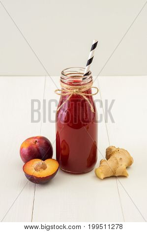 Immune booster plum and ginger juice in bottle on white wooden background