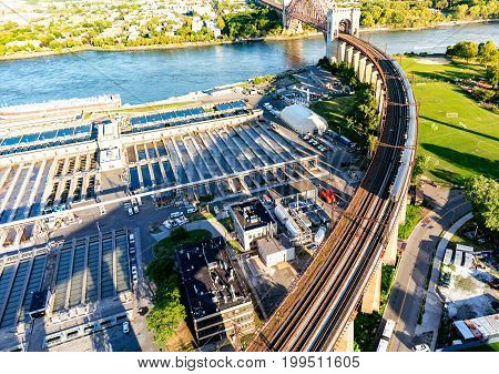 Aerial view of the of a train crossing the Hell Gate Bridge over the East River in New York City