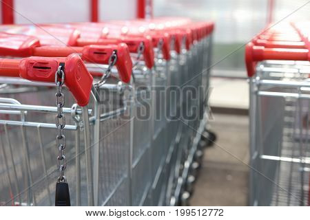 Red handles of shopping trolleys standing in row near hypermarket. Shopping trolley close-up. Shopping concept.