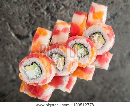 Roll made with tuna, salmon and scallop over concrete background