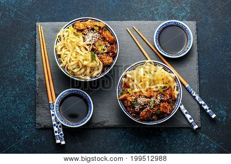 Chicken teriyaki on dark background with balsamic sauce and sesame seeds. Asian food. Noodles, chicken and soy sauce. Top view.