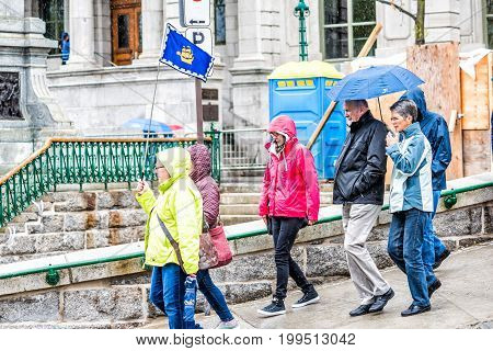 Quebec City Canada - May 30 2017: Closeup of tour group of people walking in heavy rain with umbrellas