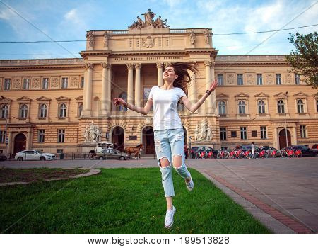 Happy jumping student girl in a city park on the background of a university building