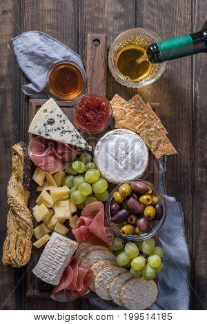 Cheese plate served with grapes, jam, prosciutto and crackers on a wooden background