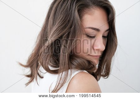 Teen girl portrait with shy expression on face over white background