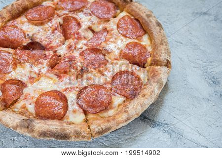 Italian Pepperoni pizza with salami on dark wooden background top view. Italian traditional food. Popular street food.