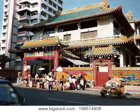 SINGAPORE / CIRCA 1990: Hawkers sell their wares outside the entrance to the Kwan Im Thong Hood Cho Temple.