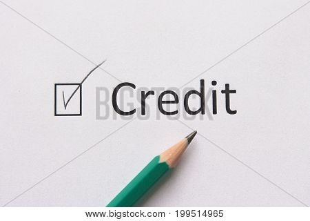 Complete loan payments. Pay  loan. word CREDIT is written on white paper in gray pencil.
