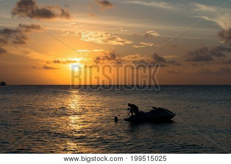 Wide angle picture from the beach of a man silhouette sitting on jet ski during sunset time with cloud sky at Maafushi in Maldives.