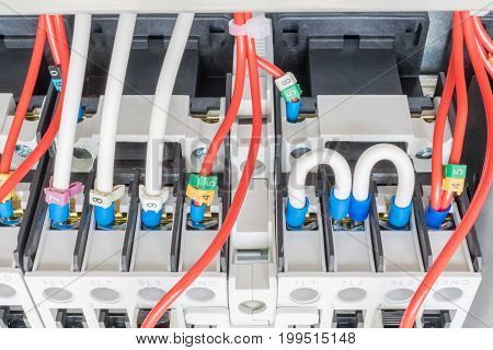 Several contactors are mounted on mounting panel. To them attached to an electrical wire lugs and number coded. Two wires are connected by a semicircle.Professional Assembly electric rack.