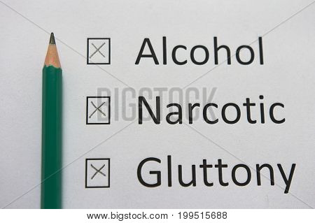 Harmful habits: alcohol, drugs, gluttony are written on white paper in gray pencil. Get rid of bad habits.