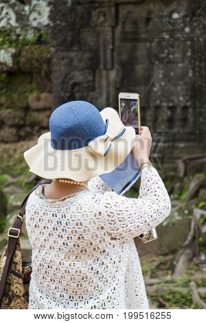 Woman with a hat and a handbag taking pictures with mobile phone.