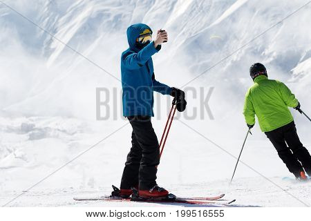 Skier makes selfie on camera phone and snow mountains in fog at background. Caucasus Mountains in winter Georgia region Gudauri.