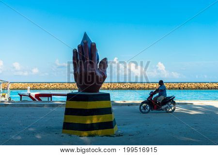 MAAFUSHI MALDIVES - MARCH 01 2016: Horizontal picture of native local man driving a motorcycle at the main sand street of Maafushi in Maldives. Local art in hands shape.