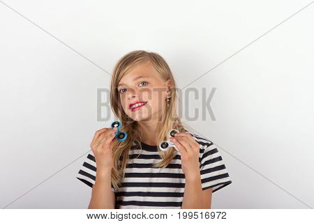 Beautiful young girl playing with two fidget spinners