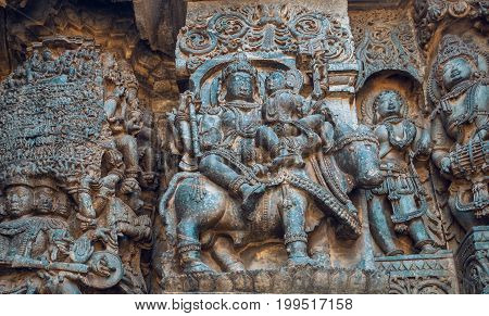 Ornate relief of Siva and Parvathi sitting on bull and money other stories in stone. 12th century Hoysaleshwara temple in Halebidu, India