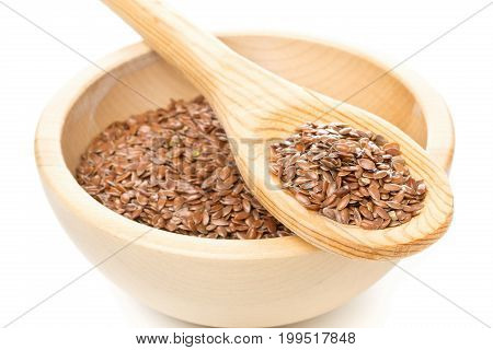 Raw unprocessed linseed or flax seed in wooden bowl and wood spoon over white background