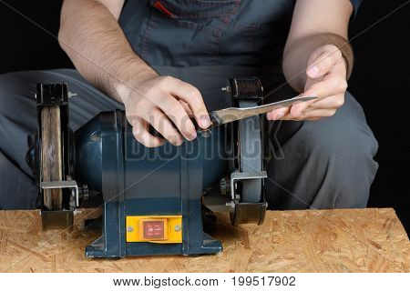 A man in working clothes hones professional sharpening kitchen knife isolated