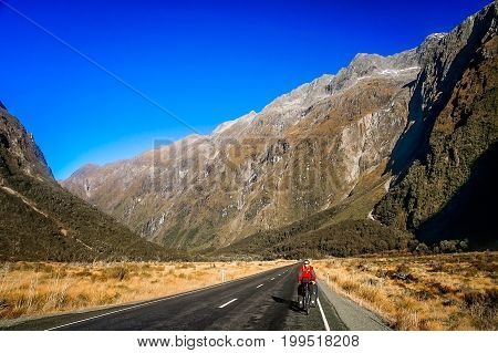 Woman on a cycle touring trip on a road leading to the Milford Sound, New Zealand