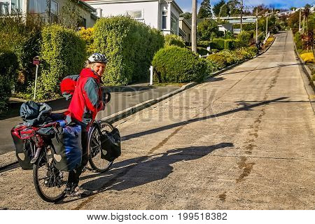 Female cyclist attempting to cycle uphill on the Baldwin street - the steepest street in the world, Dunedin, New Zealand
