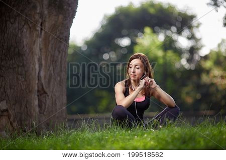 Young sportswoman posing on green grass with headphones looking away. Fitness woman. Fitness woman in the city park. Caucasian female fitness model working out in the morning