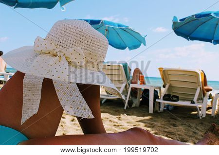 A white hat with wide brim is put on the bent knee of a woman lying on a deckchair on the beach.