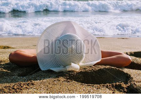 The woman lies on the sand against the background of the sea surf in a white hat with wide brim.