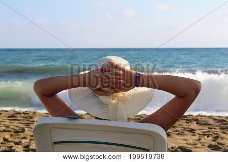 A woman sits in a deck chair against the background of a sea surf in a white hat with wide brim.