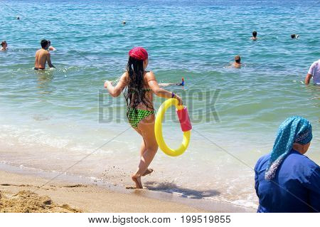 July, 2017 - A girl with a yellow inflatable circle runs to the water on Cleopatra Beach (Alanya, Turkey).