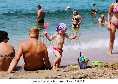 July, 2017 - A little girl is playing with beach toys on Cleopatra Beach (Alanya, Turkey).