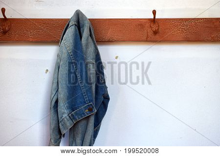 An old worn and faded denim jacket hanging on a coat hook.