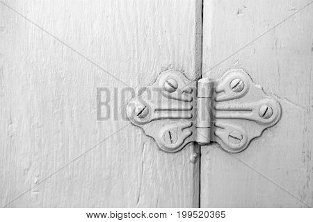 A close up image of an antique decorative door hinge painted white.