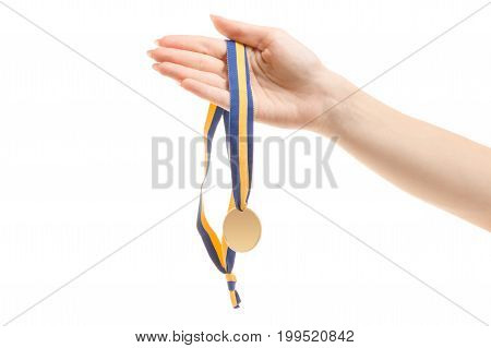 Gold medal on a string in female hands on a white background isolation