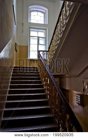 Dark vintage staircase interior in old building, stair with forged railing, big window with day light