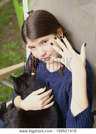 teenager girl with two plaits show black manicure with black cat on summer background