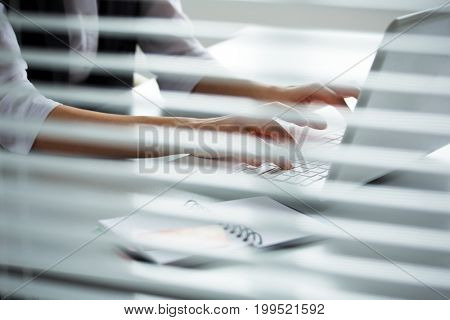 Close-up of hands of businesswoman typing on a laptop.
