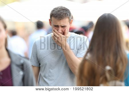 Front view portrait of a sad boy walking on the street being ignored by the crowd